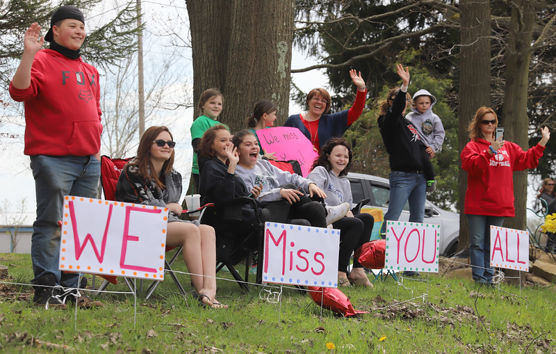 Members of the McCloskey, Saul, Slattery and Halstead families wave to teachers in Thursday's Moraine Elementary teacher caravan. Seb Foltz/Butler Eagle
