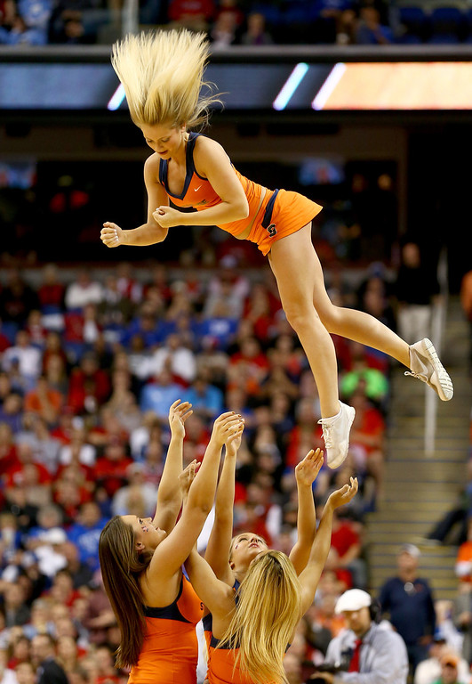. The Syracuse Orange cheerleaders in action during the quarterfinals of the 2014 Men\'s ACC Basketball Tournament at Greensboro Coliseum on March 14, 2014 in Greensboro, North Carolina.  (Photo by Streeter Lecka/Getty Images)