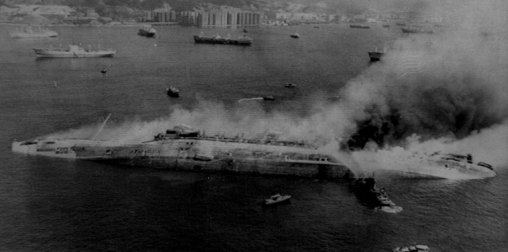 Description of . The former passenger liner Queen Elizabeth lies capsized and smoking in Hong Kong harbor on Jan. 18, 1972 while a fireboat sprays water on the smoking hull. The Queen Elizabeth, in Hong Kong to be converted into a floating university, caught fire on Sunday.