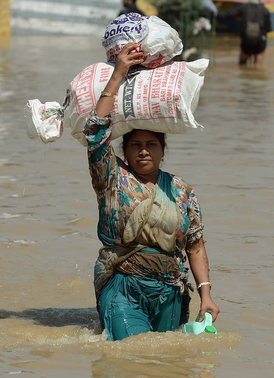 . A Kashmiri woman carries her belongings on her head as she makes her way through the floodwaters in Srinagar on September 10, 2014.  AFP PHOTO/ PUNIT PARANJPE/AFP/Getty Images