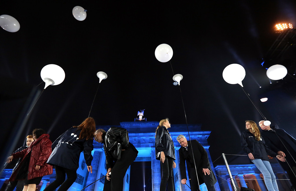 . BERLIN, GERMANY - NOVEMBER 09: German President Joachim Gauck (C R), German singer-songwriter and former East German dissident Wolf Biermann (C L) and Polish Solidarity (Solidarnosc) Leader Lech Walesa (R) launch balloons from the Lichtgrenze light installation during celebrations for the 25th anniversary of the fall of the Berlin Wall at the Brandenburg Gate on November 9, 2014 in Berlin, Germany. The city of Berlin is commemorating the 25th anniversary of the fall of the Berlin Wall from November 7-9 with an installation of 6,800 lamps coupled with illuminated balloons along a 15km route where the Wall once ran and divided the city into capitalist West and communist East. The fall of the Wall on November 9, 1989, was among the most powerful symbols of the revolutions that swept through the communist countries of Eastern Europe and heralded the end of the Cold War. Built by the communist authorities of East Germany in 1961, the Wall prevented East Germans from fleeing west and was equipped with guard towers and deadly traps.  (Photo by Adam Berry/Getty Images)