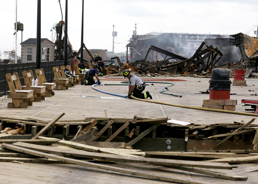 . A firefighter unhooks two hoses at the place where emergency workers broke through the recently repaired boardwalk in efforts to stop a fire that broke out a day earlier at the Seaside Park boardwalk, Friday, Sept. 13, 2013, in Seaside Park, N.J. (AP Photo/Julio Cortez)
