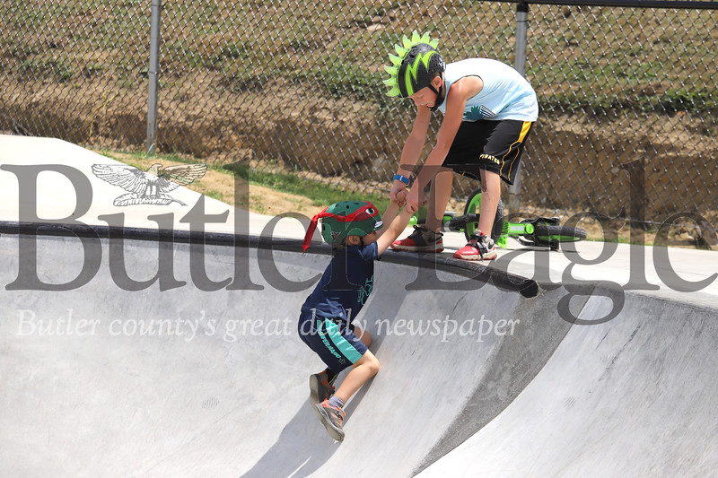 Levi King, 8, of Zelienople helps Chace Pedicone, 5, of Seven Fields out of the swimming pool feature at the Zelienople Memorial Skatepark Tuesday. Seb Foltz/Butler Eagle