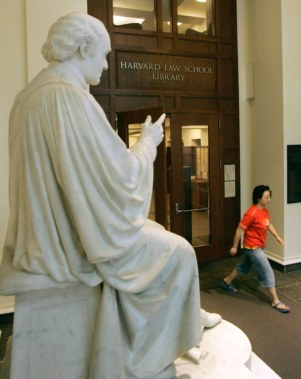 . An unidentified woman walks past a statue of Supreme Court justice Joseph Story, a Harvard Law School graduate, leaves Langdell Hall, the Harvard Law Library, on the campus of the Harvard Law School in Cambridge, Mass., Monday, Aug. 1, 2005.  Black-robed for two centuries, the Supreme Court justices could be sporting a new color next term: crimson.  That would be to honor Harvard Law School, which if John Roberts is confirmed, could make an unprecedented boast: five of its graduates serving on the high court simultaneously. A sixth justice, Ruth Bader Ginsberg, attended Harvard Law but finished her degree at Columbia.  (AP Photo/Charles Krupa)