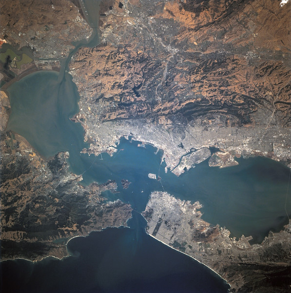 Astronaut Tom Jones: All of us enjoyed our repeated views of San Francisco Bay and the San Andreas Fault, running left to right in the bottom of the image below. Steve Smith and Jeff Wisoff were both Stanford grads, and Mike Baker hails from this part of the country. Urban growth patterns and the many tectonic faults and features were the focus of our radar and camera studies here.NASA: Photographed through the Space Shuttle Endeavour's flight deck windows, the heavily populated San Francisco Bay area is featured in this 70mm frame. The relatively low altitude of Endeavour's orbit (115 nautical miles) and the use of a 250mm lens on the Hasselblad camera allowed for capturing detail in features such as the Berkeley Marina (frame center). The region's topography is well depicted with the lowland areas heavily populated and the hills much more sparsely covered. The Oakland Hills in the right lower center appear to be re-vegetated after a devastating fire. The Golden Gate Recreation Area in the upper left also shows heavy vegetation. The three bridges across the main part of the bay and their connecting roads are prominent. Cultural features such as Golden Gate Park and the Presidio contrast with the gray of the city.