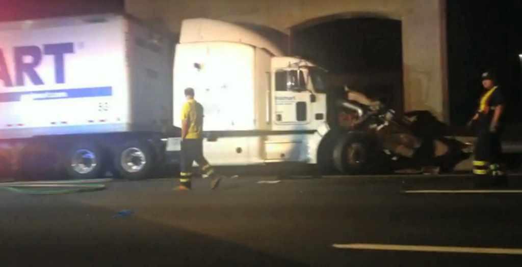 """. In this image from video the Wal-Mart truck involved in the crash of the limousine bus carrying Tracy Morgan and six other people is seen early Saturday morning June 7, 2014 on the New Jersey Turnpike at the accident scene. Morgan remained hospitalized as state and federal officials continued their investigation of the six-vehicle crash on the New Jersey Turnpike that took the life of a Morgan friend and left two others seriously injured, authorities say. Wal-Mart President Bill Simon said in a statement a Wal-Mart truck was involved and that the company \""""will take full responsibility\"""" if authorities determine that its truck caused the accident. (AP Photo/Will Vaultz Photography)"""