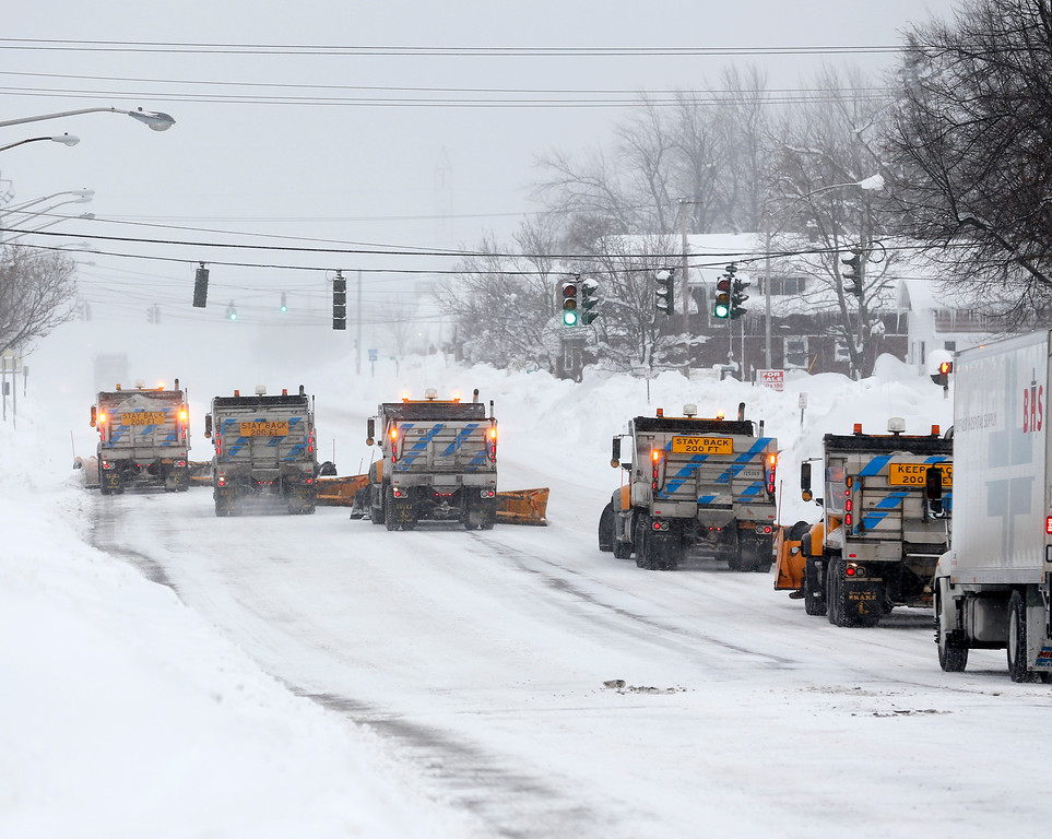 . State snowplows clear Union Road on Thursday, Nov. 20, 2014, in West Seneca, N.Y. A new blast of lake-effect snow pounded Buffalo for a third day piling more misery on a city already buried by an epic, deadly snowfall that could leave some areas with nearly 8 feet of snow on the ground when it\'s all done. (AP Photo/Mike Groll)