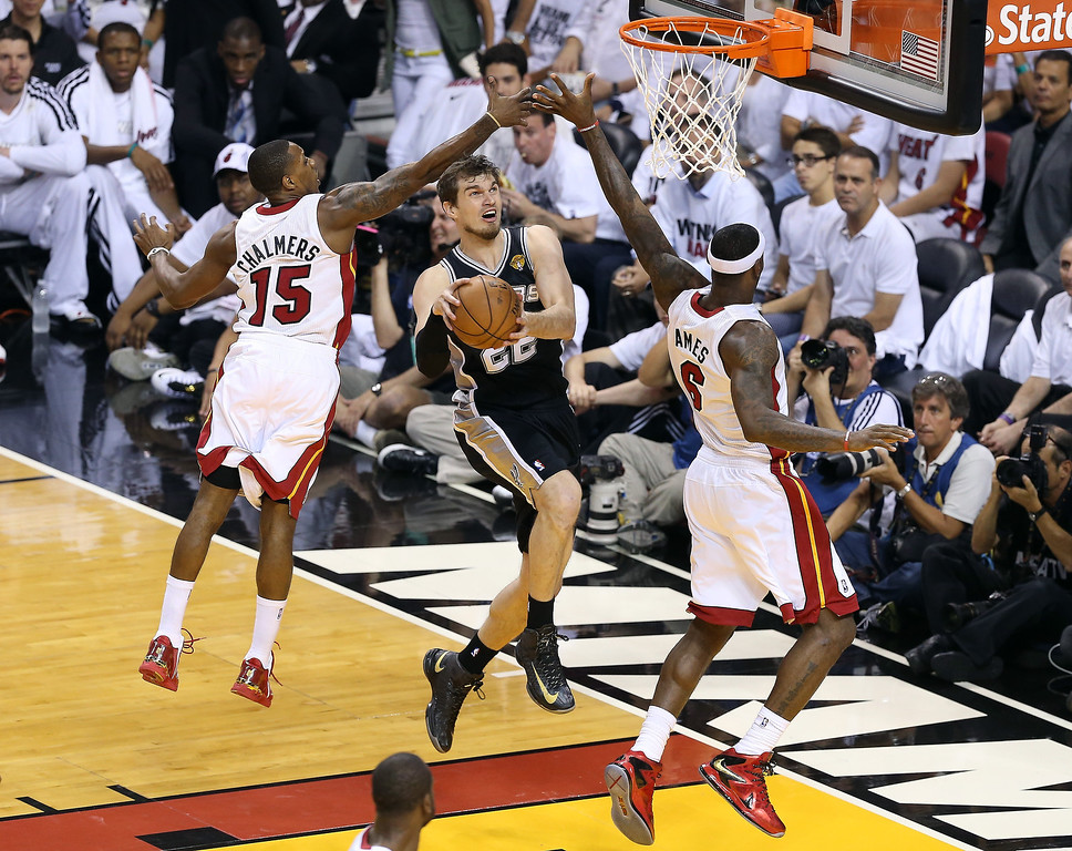 . Tiago Splitter #22 of the San Antonio Spurs goes up for a shot between Mario Chalmers #15 and LeBron James #6 of the Miami Heat in the first quarter during Game One of the 2013 NBA Finals at AmericanAirlines Arena on June 6, 2013 in Miami, Florida. (Photo by Christian Petersen/Getty Images)
