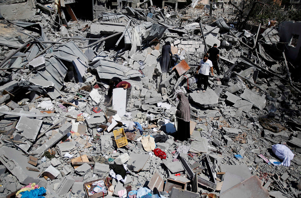 . Palestinians search the rubble their home in Beit Hanoun, Gaza Strip, Friday, Aug. 1, 2014. A three-day Gaza cease-fire that began Friday quickly unraveled, with Israel and Hamas accusing each other of violating the truce. (AP Photo/Hatem Moussa)