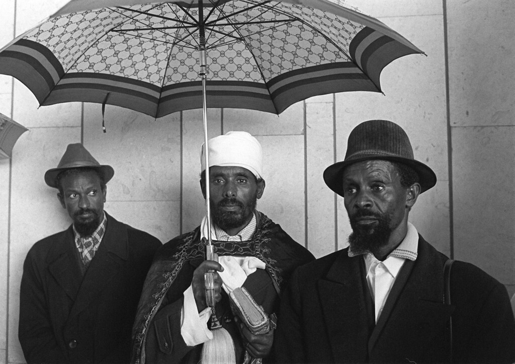 """. ASHDOD, ISRAEL - DECEMBER 23:  Newly-arrived Falashas, Ethiopian Jews, wait  23 december 1984, outside the resettlement center in Ashdod  in the Negev desert after the airlift \""""Operation Moses which brought \""""home\"""" some 10,000 Ethiopian Falashas. After the fall of Emperor Haile Selassie of Ethiopia, Israel had smuggled Falashas out of Ethiopia. Between 1980 and 1985 more than 10 000 Falashas were airlifted to resettlement camps in Israel from Sudan, to which they travelled from famine-stricken Ethiopia. ESAIAS BAITEL/AFP/Getty Images"""
