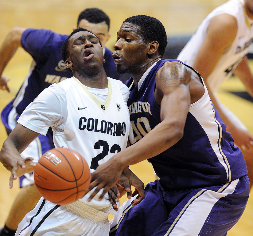 . Jaron Hopkins, left, of Colorado, collides with Shawn Kemp of Washington during the second half of an NCAA college basketball game in Boulder, Colo., Sunday, Feb. 9, 2014. (AP Photo/Daily Camera, Cliff Grassmick)