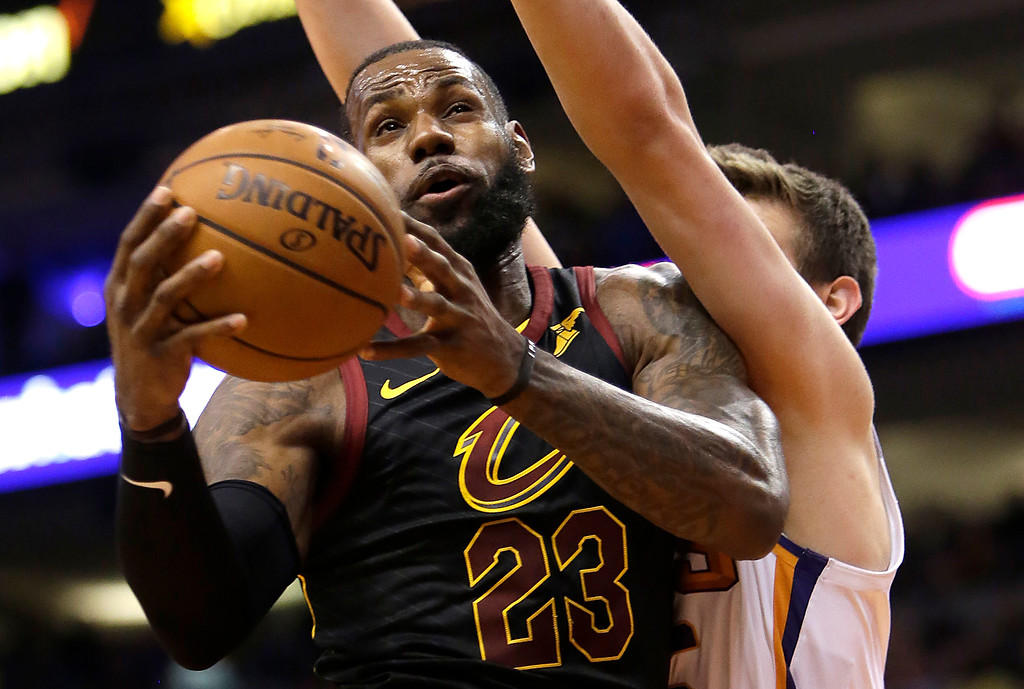 . Cleveland Cavaliers forward LeBron James (23) gets fouled by Phoenix Suns forward Dragan Bender in the first half of an NBA basketball game, Tuesday, March 13, 2018, in Phoenix. (AP Photo/Rick Scuteri)