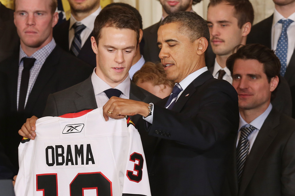 . U.S. President Barack Obama (C) is presented with a personalized jersy from Chicago Blackhawks forward Jonathan Toews during a celebration of 2013 National Hockey League champions in the East Room of the White House November 4, 2013 in Washington, DC.  (Photo by Chip Somodevilla/Getty Images)