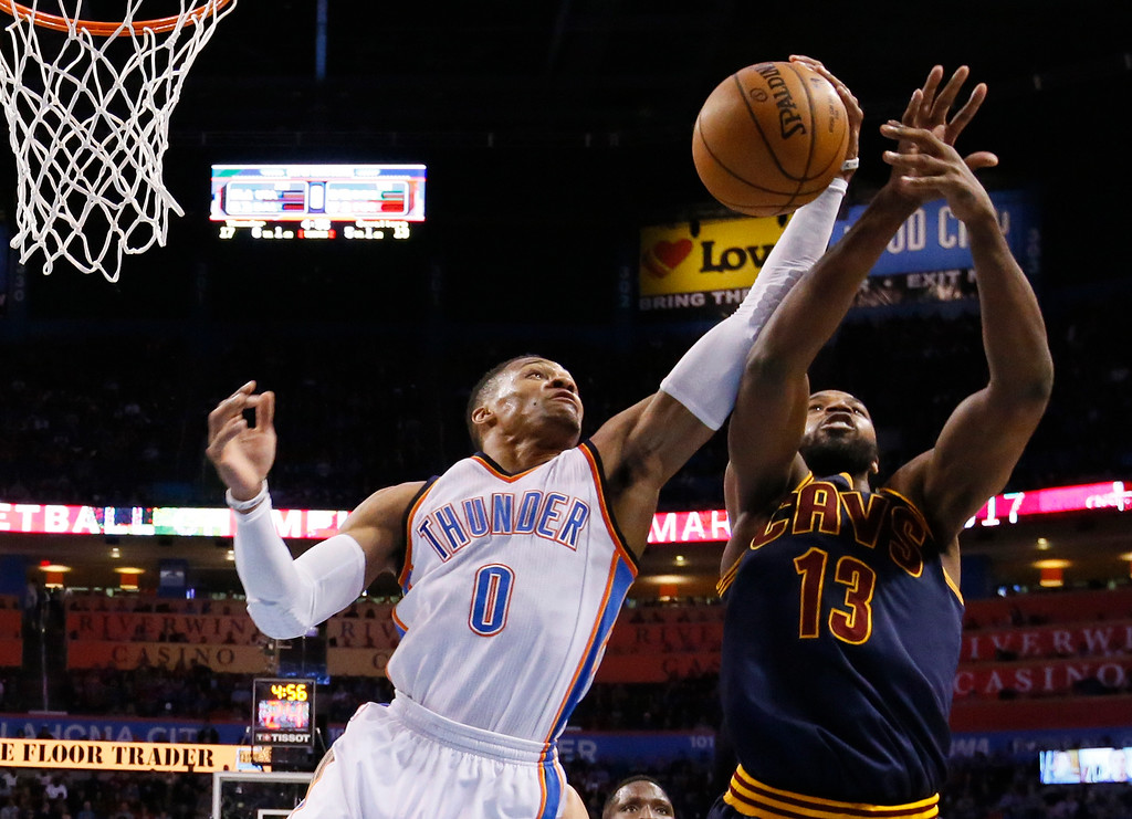 . Oklahoma City Thunder guard Russell Westbrook (0) grabs a rebound in front of Cleveland Cavaliers center Tristan Thompson (13) in the first quarter of an NBA basketball game in Oklahoma City, Thursday, Feb. 9, 2017. (AP Photo/Sue Ogrocki)