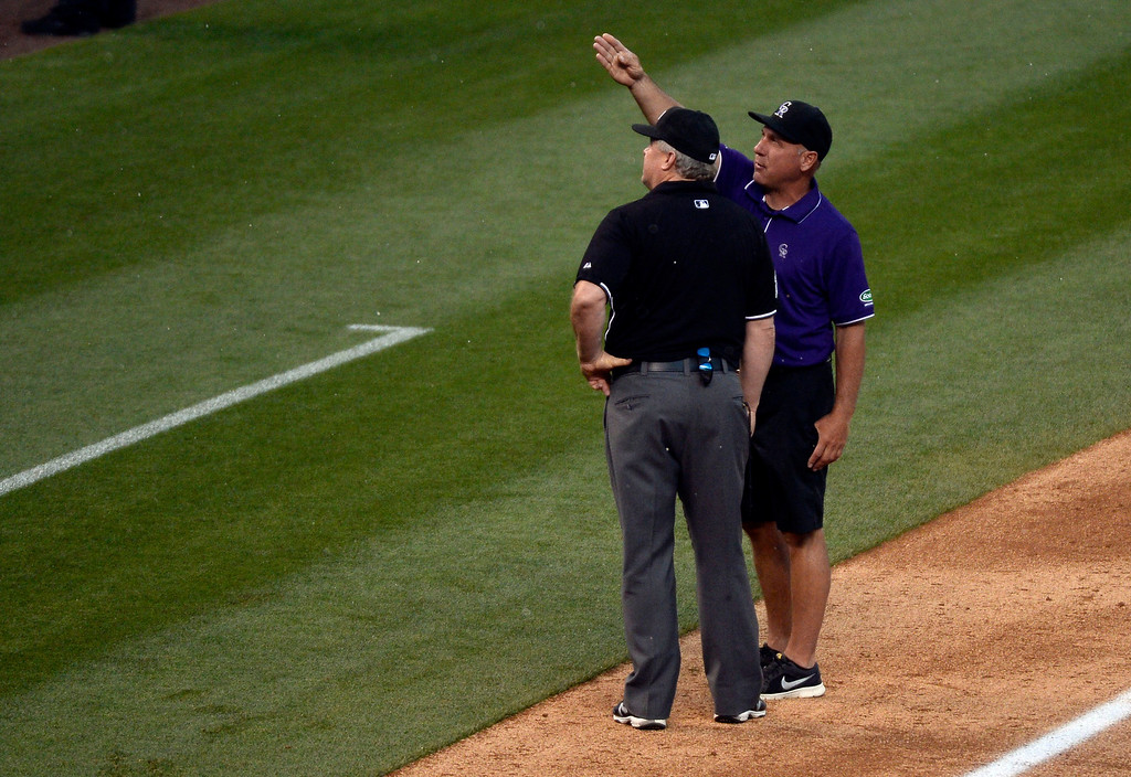 . DENVER, CO - MAY 22: Head grounds crew Mark Razum points to the sky with 1st base umpire Bill Miller as clouds swirl over the stadium at the Colorado Rockies San Francisco Giants game May 22, 2014 at Coors Field. (Photo by John Leyba/The Denver Post)