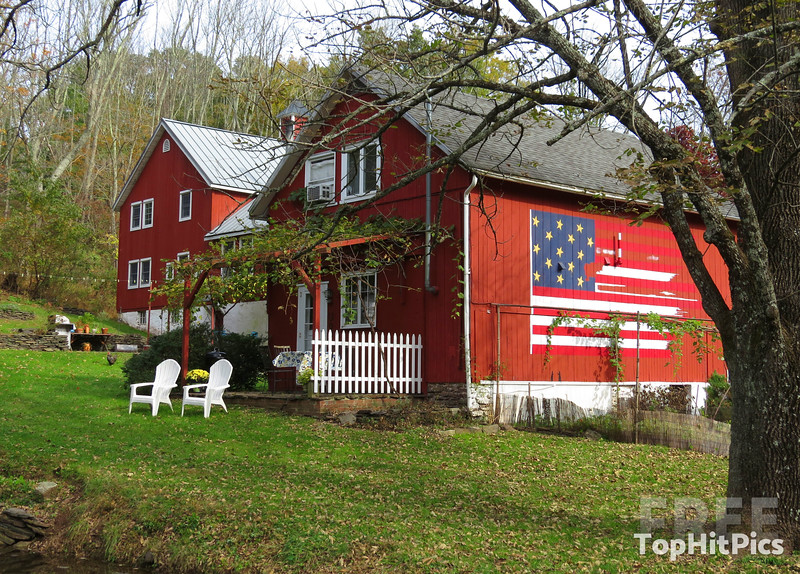 An Iconic Red American Farm House With The USA Flag On The Side, NJ