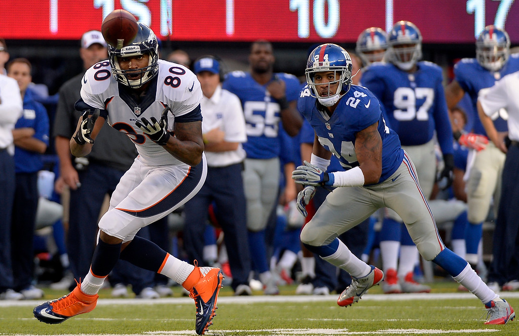 . Denver Broncos tight end Julius Thomas (80) catches a pass from Peyton Manning during the second quarter as New York Giants defensive back Terrell Thomas (24) comes in on defense September 15, 2013 MetLife Stadium. (Photo by John Leyba/The Denver Post)