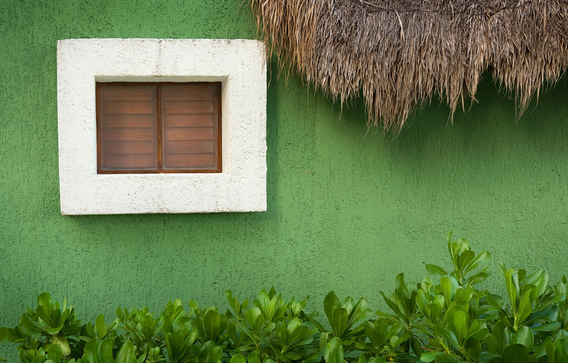 Window and Wall - Mexico  Vivid colors adorn the seaside homes of the Riviera Maya, where hand-thrown stucco, thatch roofs, and coastal vegetation meet with a crazy palette of hues and textures.