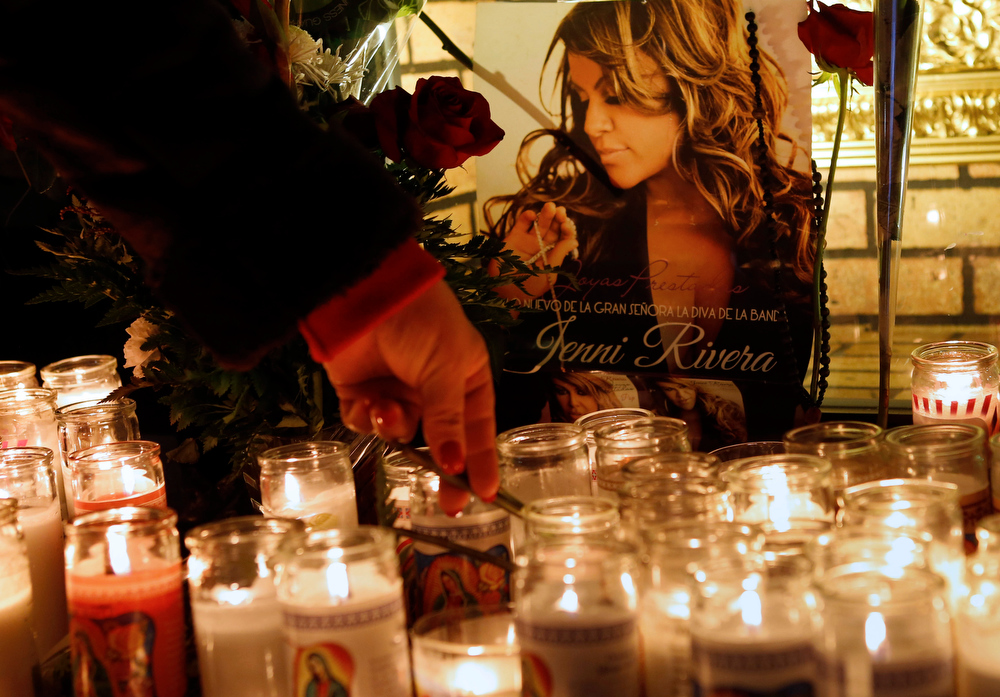 . A woman adjusts a flower in front of candles and pictures displayed in tribute to singer Jenni Rivera at the Plaza Mexico shopping center in Lynwood, Calif., early Monday, Dec. 10, 2012. Authorities have not confirmed her death, but Riveraís relatives in the U.S. say they have few doubts that she was on the Learjet 25 that disintegrated on impact Sunday in rugged territory in Nuevo Leon state in northern Mexico. (AP Photo/Patrick T. Fallon)