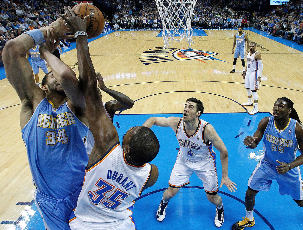 . Oklahoma City Thunder forward Kevin Durant (35) blocks a shot by Denver Nuggets center JaVale McGee (34) in front of Thunder forward Nick Collison (4) and Nuggets forward Kenneth Faried (35) in the first quarter of an NBA basketball game in Oklahoma City, Tuesday, March 19, 2013. (AP Photo/Sue Ogrocki)