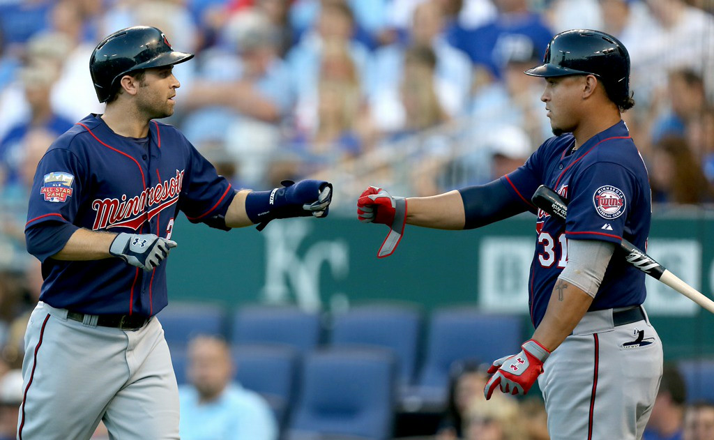 . Minnesota\'s Brian Dozier, left, celebrates with Oswaldo Arcia after scoring on Kennys Vargas\' ground out in the first inning against the Royals. (Photo by Ed Zurga/Getty Images)