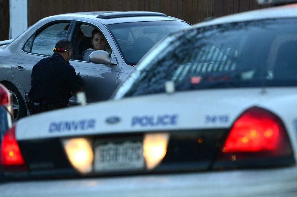 . A police officer speaks with a woman in a secure area near 40th and Lipan where a police officer was injured during what witnesses described as a red Dodge truck wrecking into a tree and a man exiting the truck who began shooting and fled on foot on Wednesday, January, 16, 2013. AAron Ontiveroz/The Denver Post