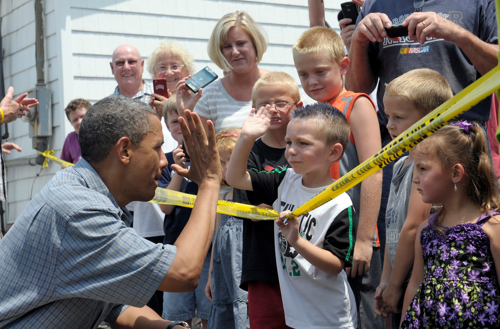 . President Barack Obama gets a high-five as he greets children outside the Kozy Corner diner in Oak Harbour, Ohio, Thursday, July 5, 2012. Obama is on a two-day bus trip through Ohio and Pennsylvania. (AP Photo/Susan Walsh)