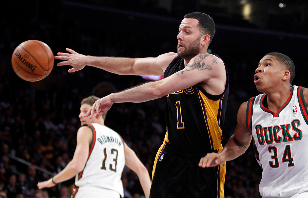 . Los Angeles Lakers guard Jordan Farmar (1) passes the ball away from Milwaukee Bucks shooting guard Giannis Antetokounmpo (34), of Greece, defending during the first half of an NBA basketball game Tuesday, Dec. 31, 2013, in Los Angeles. (AP Photo/Alex Gallardo)