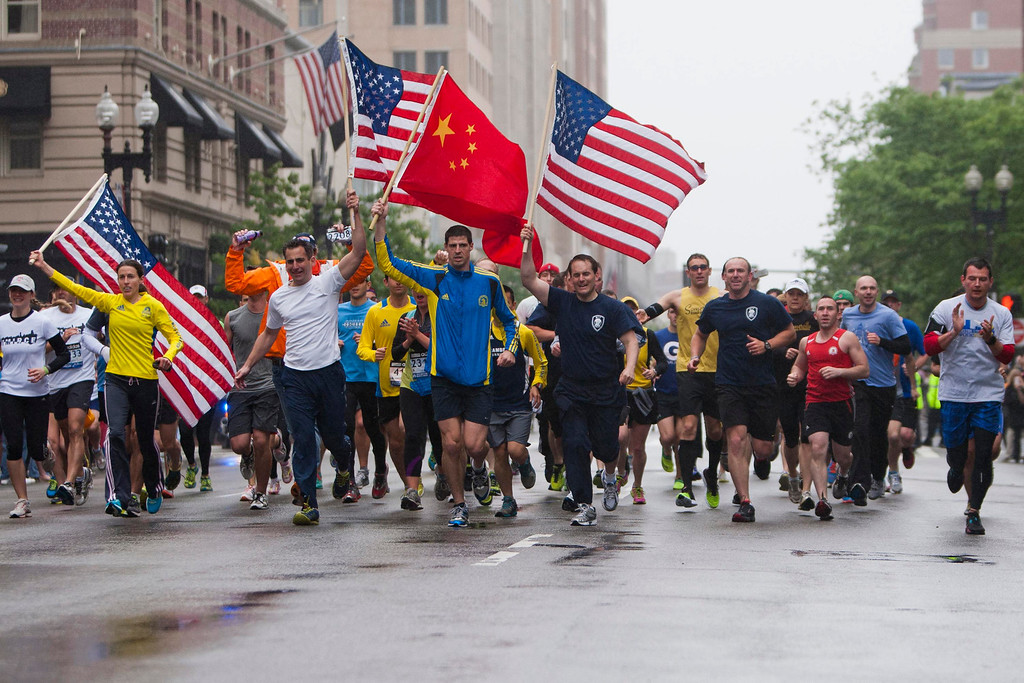 ". Runners carry American flags and a Chinese flag as they approach the finish line after completing the final mile of the Boston Marathon course during ""#onerun\"" in Boston, Massachusetts, May 25, 2013.   REUTERS/Dominick Reuter"