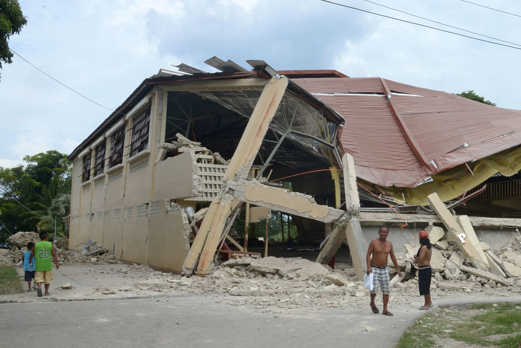 . Residents walk by a damaged gymnasium on the popular tourist island of Bohol, central Philippines on October 16, 2013 following a 7.1-magnitude earthquake in the area on October 15.   AFP PHOTO / Jay DIRECTO/AFP/Getty Images