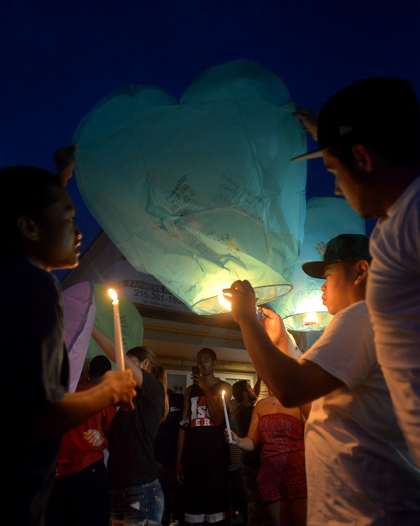 . Pat Pravongviengkham uses a candle to fill one of the  heart-shaped paper hot air balloons which were released Monday night, Aug. 25, 2014 in honor of the victim of a fatal crash on Broad St, Hatfield. Montgomery Media staff photo by Bob Raines