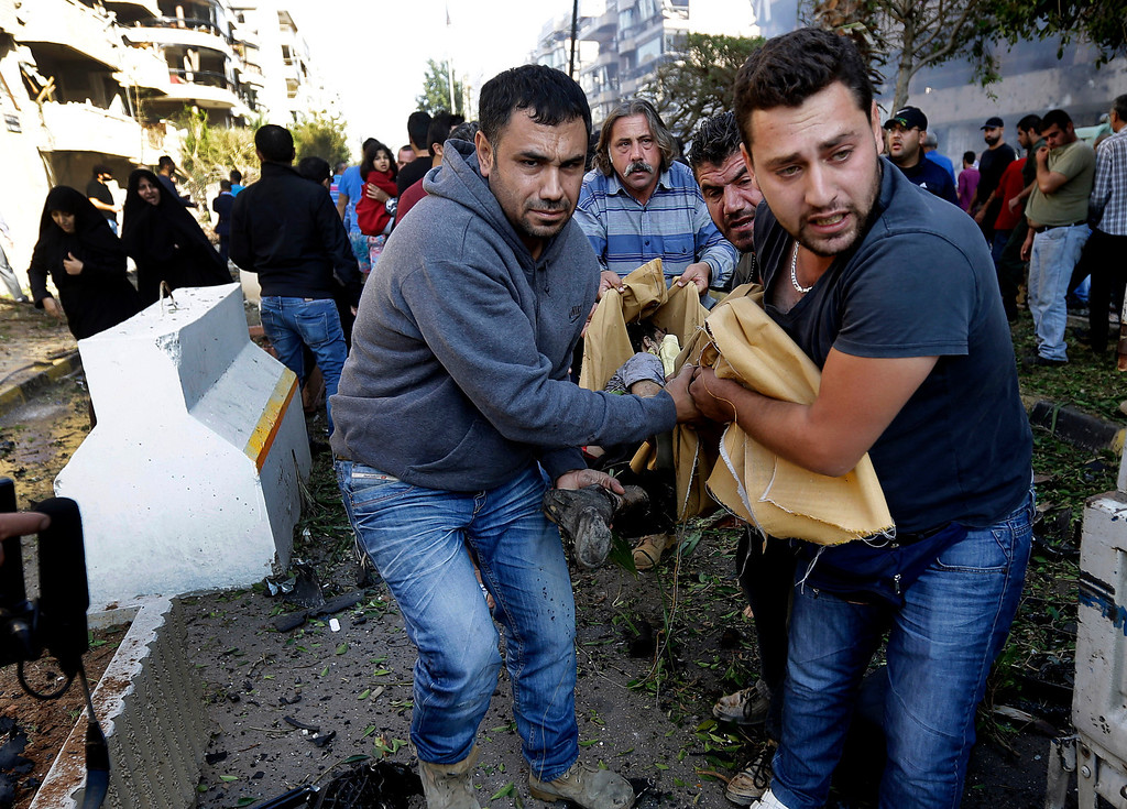 . Lebanese citizens carry a dead body, at the scene where two explosions have struck near the Iranian Embassy killing many, in Beirut, Lebanon, Tuesday Nov. 19, 2013.  (AP Photo/Hussein Malla)