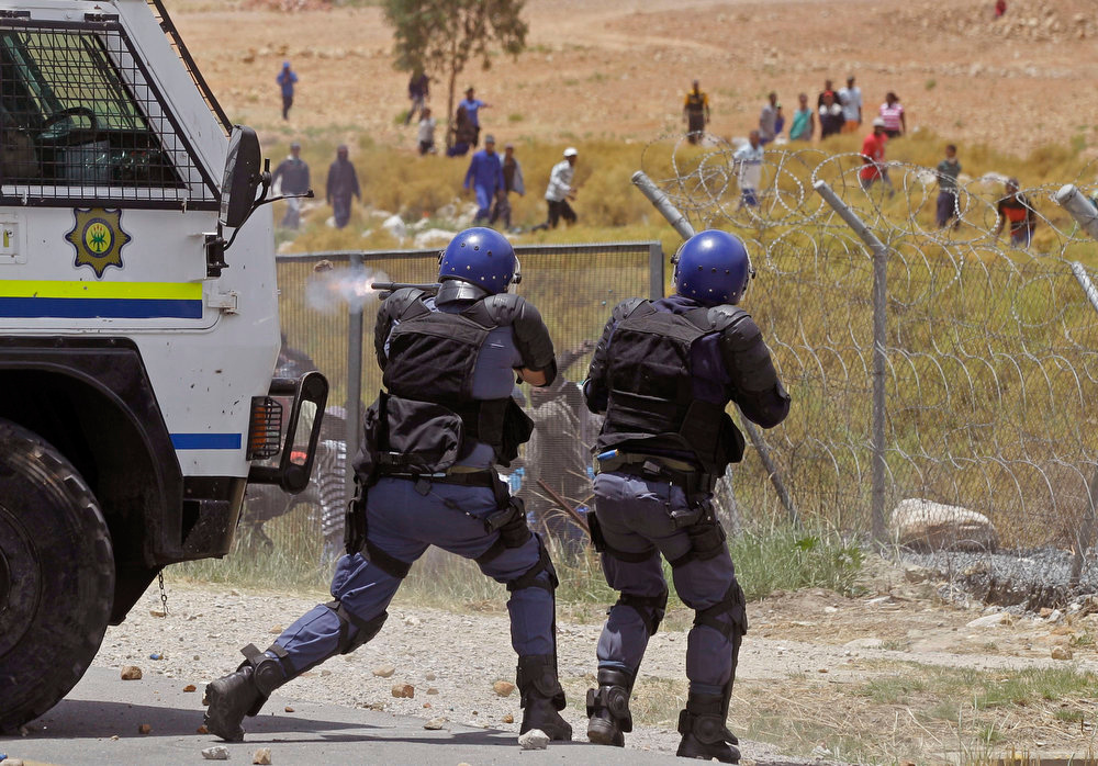 Description of . South African police fire robber bullets at the farm workers as they demonstrate in De Doorns , South Africa, Thursday, Jan 10, 2013. Striking farm workers in South Africa have clashed with police for a second day during protests for higher wages. The South African Press Association says police on Thursday fired rubber bullets at rock-throwing demonstrators in the town of De Doorns in Western Cape province, and protests were occurring in at least two other towns. (AP Photo/Schalk van Zuydam)