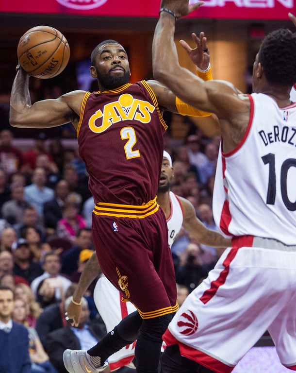 . Cleveland Cavaliers\' Kyrie Irving (2) passes as Toronto Raptors\' DeMar DeRozan (10) defends during the first half of an NBA basketball game in Cleveland, Tuesday, Nov. 15, 2016. The Cavaliers won 121-117. (AP Photo/Phil Long)