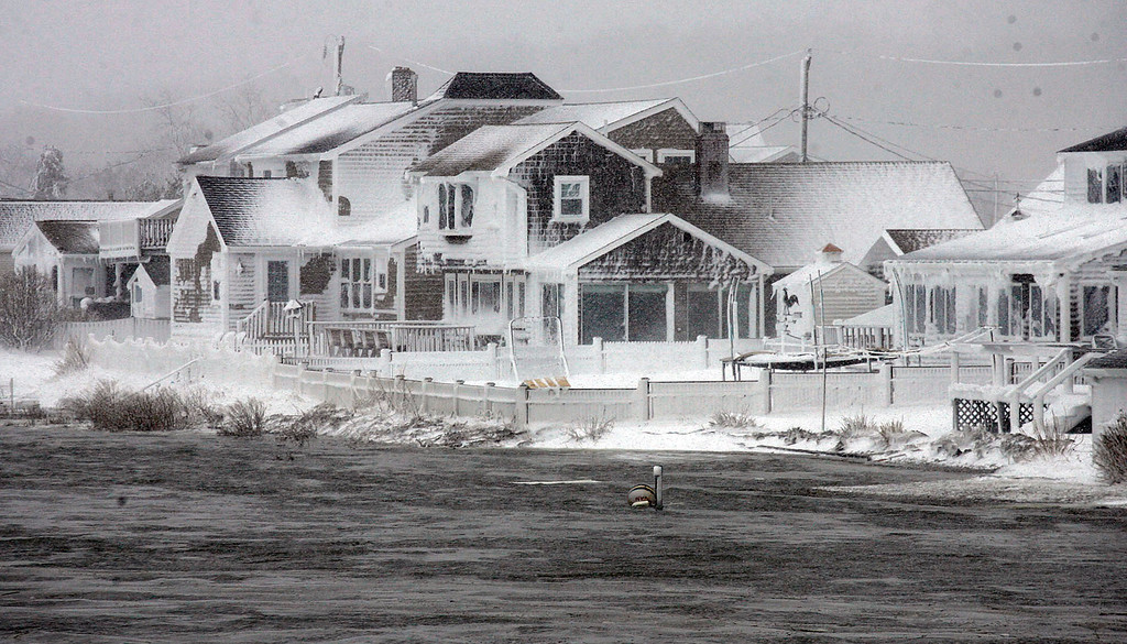 . Wet snow coats houses along the South River at high tide in the Humarock coastal neighborhood of Scituate Mass. on Saturday, Feb. 9, 2013. A behemoth storm packing hurricane-force wind gusts and blizzard conditions swept through the Northeast overnight. (AP Photo/The Patriot Ledger, Greg Derr)