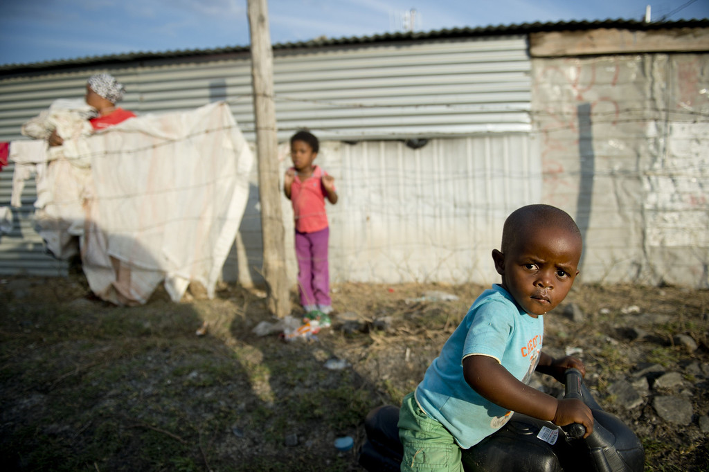 . A child plays on a bicycle on July 9, 2013 in the Nkaneng shantytown next to the platinum mine, run by British company Lonmin, in Marikana. On August 16, 2012, police at the Marikana mine open fire on striking workers, killing 34 and injuring 78, during a strike was for better wages and living conditions. Miners still live in dire conditions despite a small wage increase.  ODD ANDERSEN/AFP/Getty Images