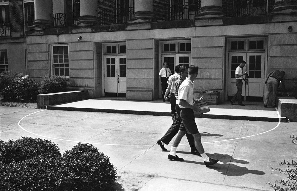 . Students stroll by the front of Foster auditorium on the campus of the University of Alabama in Tuscaloosa, Ala., June 10, 1963, where two black students are scheduled to register tomorrow for classes. It is at this spot Alabama Gov. George Wallace has vowed to stand in the door to bar their entrance. A white semi-circle has been painted on the walkway where Wallace apparently plans to halt the two students. (AP Photo)