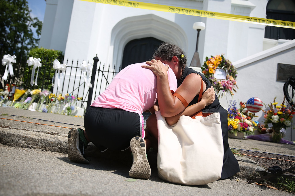 . Women comfort each other as they mourn in front of the Emanuel African Methodist Episcopal Church after a mass shooting at the church that killed nine people on June 19, 2015 in Charleston, South Carolina. Dylann Roof, 21 years old, is suspected of killing nine people during a prayer meeting in the church, which is one of the nation\'s oldest black churches in Charleston.  (Photo by Joe Raedle/Getty Images)