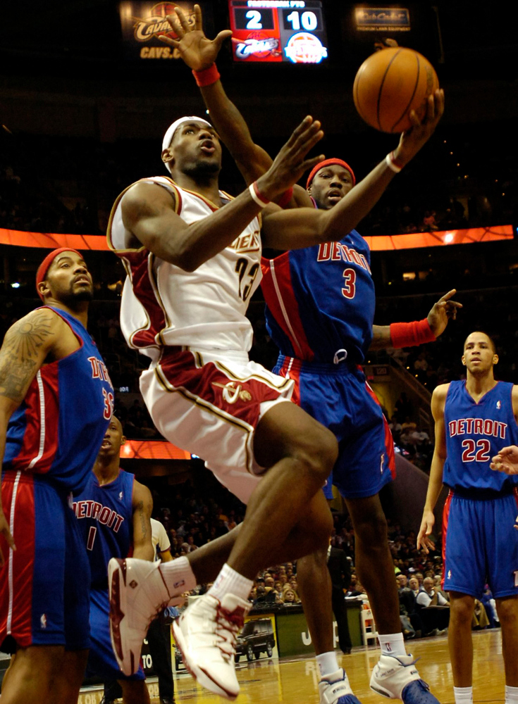 . PHOTO BY DAVID RICHARD LeBron James slips past Rasheed Wallace, left, and Ben Wallace last night in the first half.
