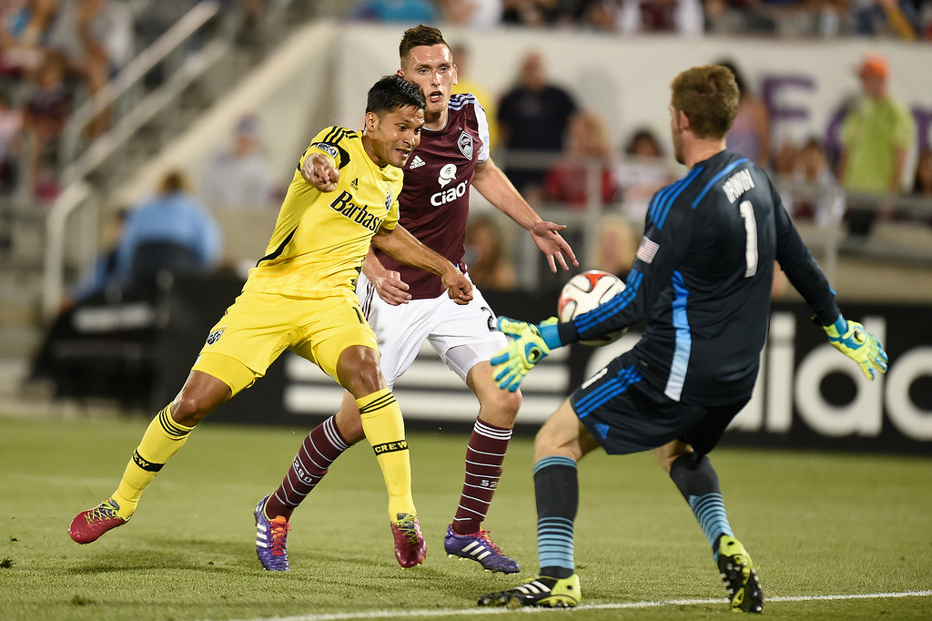 . Clint Irwin #1 of the Colorado Rapids makes a save against Jairo Arrieta #19 of the Columbus Crew as Shane O\'Neill #27 of the Colorado Rapids tries to stop him during the second half of an MLS game at Dick\'s Sporting Goods Park on July 4, 2014, in Commerce City, Colorado. (Photo by Daniel Petty/The Denver Post)