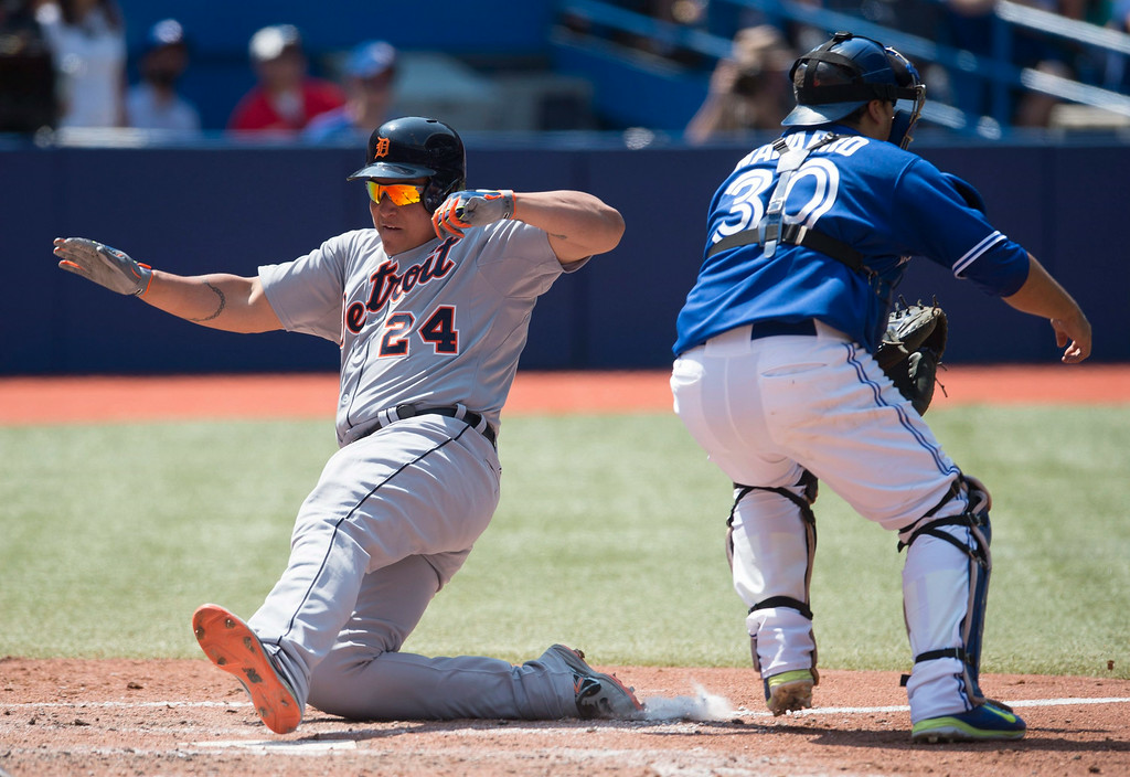. Detroit Tigers\' Miguel Cabrera, left, slides safely past Toronto Blue Jays catcher Dioner Navarro to score on Victor Martinez\'s two-RBI double in the sixth inning of a baseball game in Toronto on Saturday, Aug. 9, 2014.  (AP Photo/The Canadian Press, Darren Calabrese)