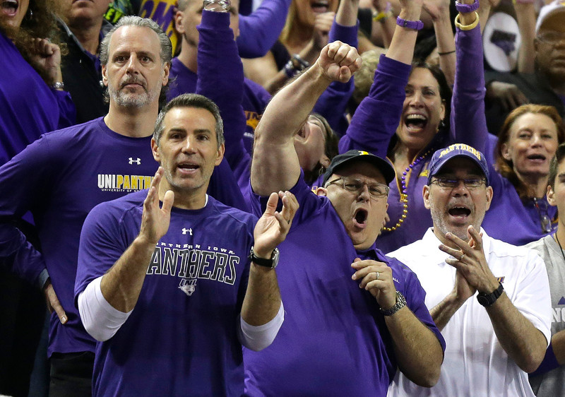 . Northern Iowa fans, including former NFL football quarterback Kurt Warner, front left, cheer during the first half of an NCAA tournament college basketball game between Wyoming and Northern Iowa in the Round of 64 in Seattle, Friday, March 20, 2015. Northern Iowa beat Wyoming 71-54. (AP Photo/Ted S. Warren)
