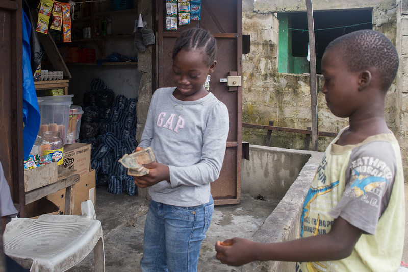 Monrovia, Liberia October 6, 2017 - Jacqueline Clinton,  a student in the REVSLA program who owns her own general store. works with her daughter.