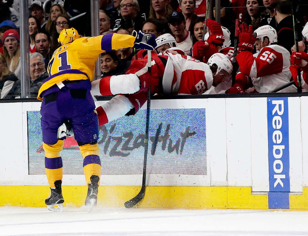 . Los Angeles Kings center Jordan Nolan, left, knocks Detroit Red Wings defenseman Danny DeKeyser into the bench during the first period of an NHL hockey game in Los Angeles, Tuesday, Feb. 24, 2015. (AP Photo/Chris Carlson)