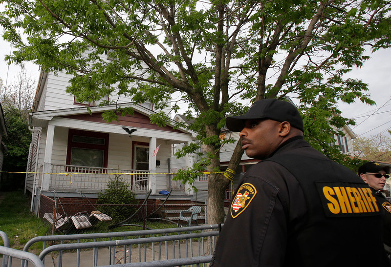. A sheriff deputy stands outside a house where three women escaped Tuesday, May 7, 2013, in Cleveland. Three women who went missing separately about a decade ago were found in the home Monday just south of downtown and likely had been tied up during years of captivity, said police, who arrested three brothers. (AP Photo/Tony Dejak)