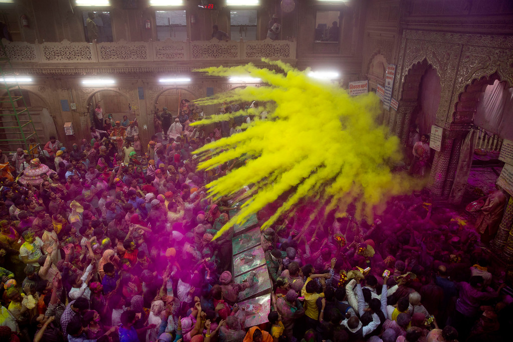 . Hindu devotees throw colored powder on each other inside Banke Bihari temple during Holi festival celebrations in Vrindavan, India, Wednesday, March 8, 2017. Holi, the festival of colors celebrates the arrival of spring among other things. (AP Photo/Manish Swarup)