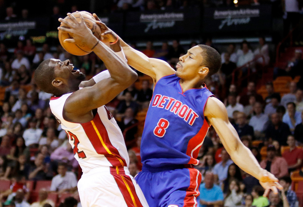 . Miami Heat forward James Ennis, left, is fouled by Detroit Pistons guard Spencer Dinwiddie (8) in the first half of an NBA basketball game, Sunday, March 29, 2015, in Miami. (AP Photo/Joe Skipper)