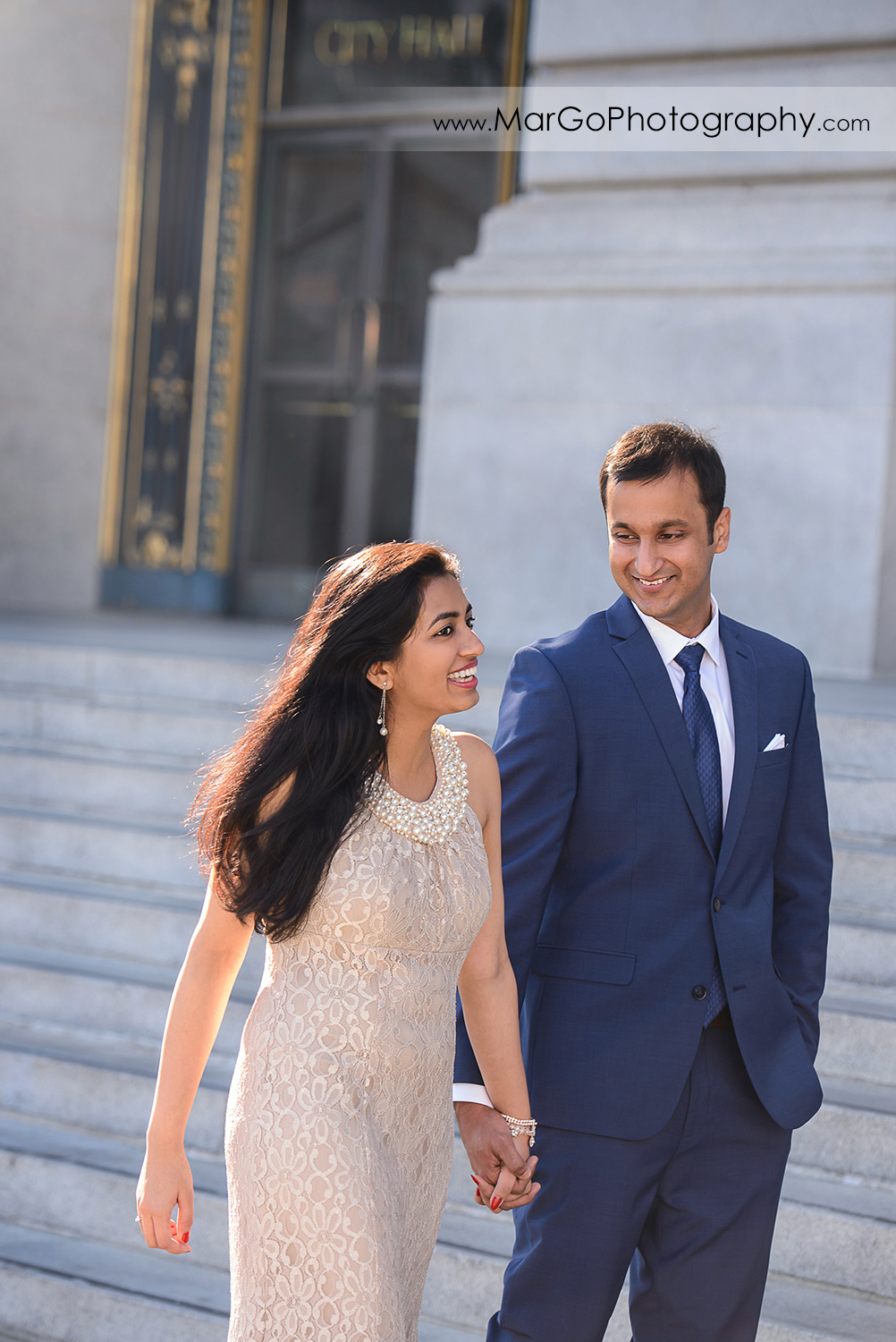woman in beige dress and man in navy blue suit holding hands and walking in front of San Francisco City Hall