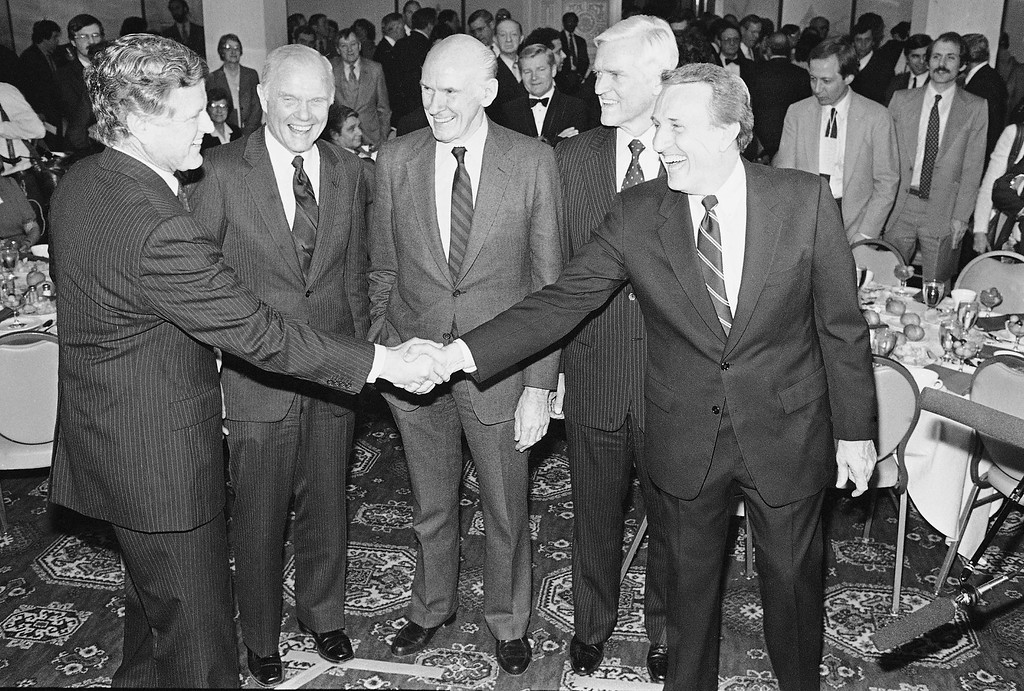 . Sen. Edward Kennedy, D-Mass, left, shakes hands with Sen. Dale Bumpers, D-Ark., right, as senators, from second left, John Glenn, D-Ohio; Alan Cranston, D-Calif.; and Ernest Hollings, D-S. Car., look on at the Democratic State Committee annual fund-raising dinner, Thursday, March 3, 1983, Boston, Mass. With the exception of Kennedy, the others are party presidential hopefuls. (AP Photo)