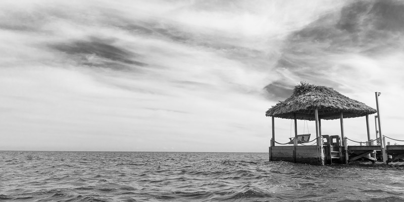 Pier with thatched roof structure, Caribbean Sea, Turneffe Island, Belize